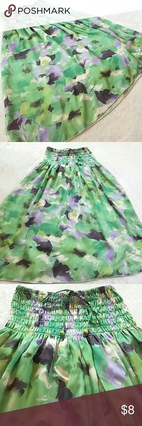 """Lapis Watercolor Tube Dress/Skirt Pretty tube dress or long skirt from Lapis. This features a floral-ish, watercolor design in various shades of green, purple, cream and charcoal. Due to unique print there are variations in material. Smocked top with tie. Flowy fit. Lined. 100% poly. There a couple of very tiny runs on the skirt which aren't noticeable, otherwise in EUC. 12"""" top unstretched. About 33"""" long. Sized OS on tag. Lapis Skirts A-Line or Full"""
