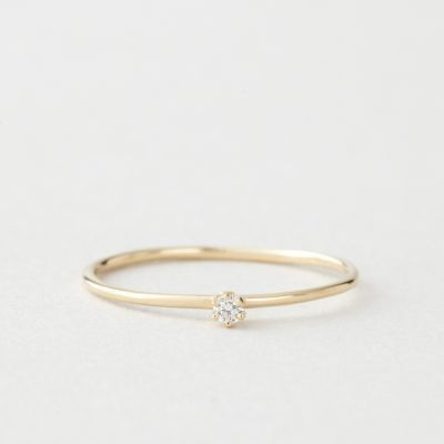 Simple and delicate 18k yellow gold band with a tiny faceted diamond solitaire.    • 1mm band with  • 0.03 carat diamond  • made in New York