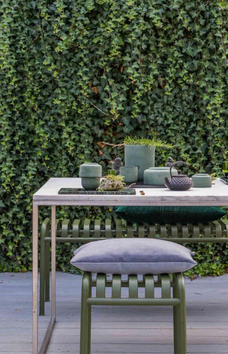 Buitenruimtes - door Glotti Press.  De Klimop, die alle vrijheid krijgt, fungeert als geluiddemper en oogt bijna als behang. De tafel van roestvrij staal heeft een marmeren blad en is op bestelling ontworpen door de lokale smid. De groene Palissade-stoel en -bank zijn van Hay, het kussen is van Louise Roe. De tafel is gedekt met jadegroene keramiek van Louise Roe op een marmeren plaat van Broste Copenhagen.
