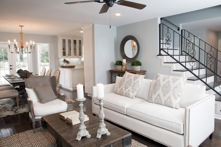 The Blount's new living room is serene with a light gray-green paint, a new built-in, and distressed wood floors, as seen on Fixer Upper. A wall once prevented guests from entering directly from the front door and another separated the living room from the dining room.
