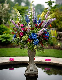 Brides: Jewel-toned Bloom Wedding Centerpiece. A lush arrangement of eremurus, hybrid delphinium in deep blue and lavender, peonies, black magic roses, astilbe, camellia leaves, veronicas, autumn hydrangea, electric blue hydrangea decorate a fountain set in the courtyard of the reception location.