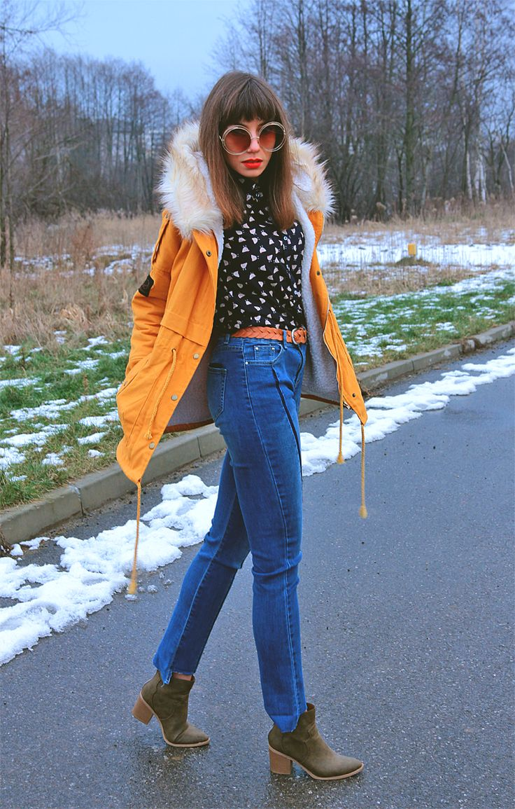seventies inspired outfit: mustard parka jacket, chicken pattern shirt, high waisted jeans and large round sunglasses