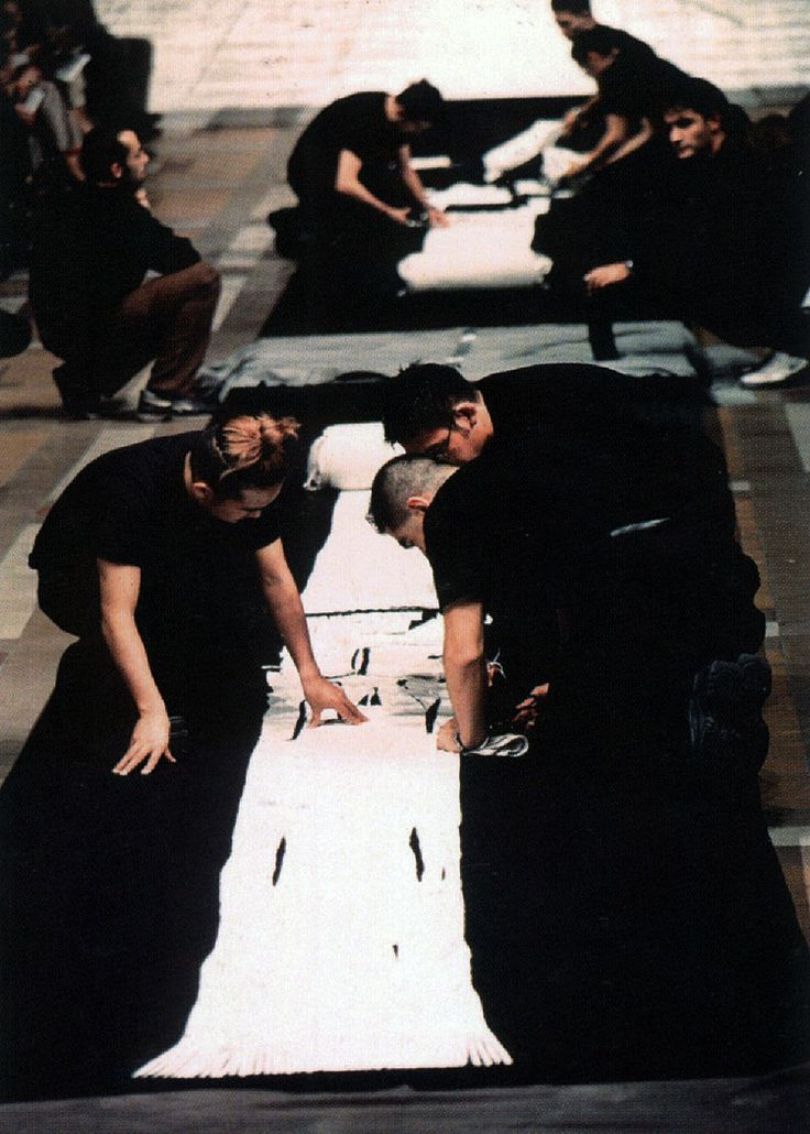 Issey Miyake has always had a commitment to innovative design. His current preoccupation, A-POC, is a long tube of fabric that doesn't require sewing and is cut by the customer without wasting any fabric. The photo depicts a catwalk demonstration of the product in 1999.