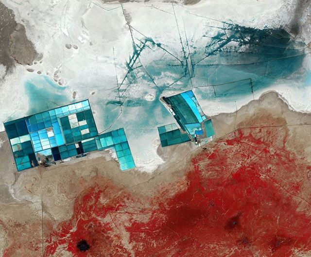 The Sentinel-2A satellite takes us over western India to a seasonal salt marsh known as the Rann of Kutch, in the Gujarat state. One of the largest salt deserts in the world, the area fills with water during the summer monsoon season. During the drier winter, the vast white desert is a popular tourist destination, particularly for the Rann Utsav festival centred around a luxury 'tent city', visible in the central-right part of the image as a series of semi-circles. Large salt evaporation…