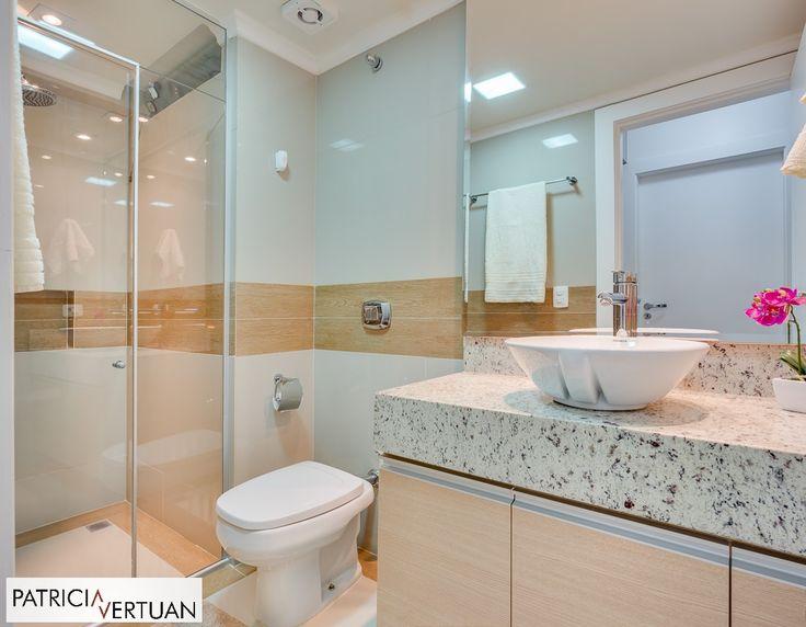 Banheiro social reformado com porcelanato bege e porcelanato imitando madeira. Tampo em granito branco aqualux e a marcenaria foi desenhada especialmente para o projeto.
