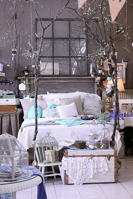 An old mantle as the headboard and tree branches as the posts around the bed.