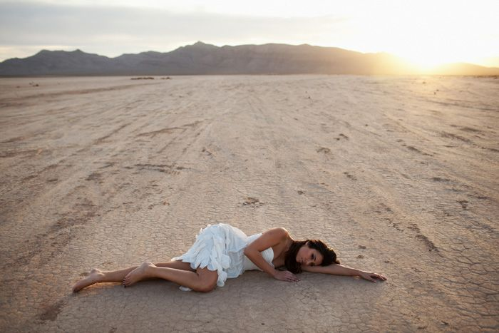 Maiden out in the desert wearing white dress