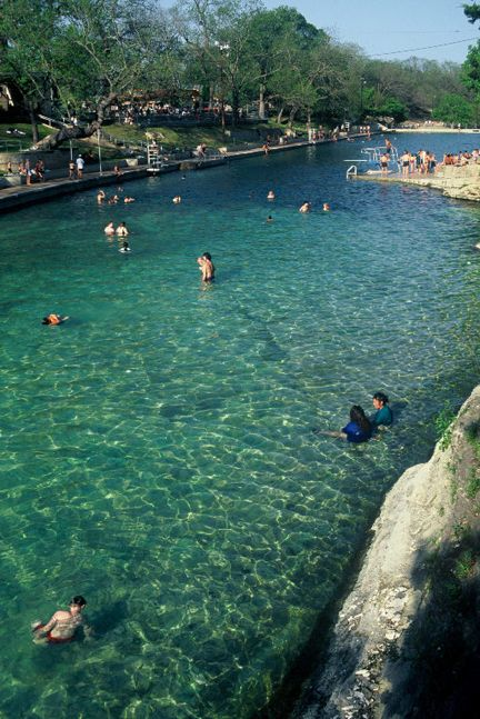 The cool water of Barton Springs pool invites people of all ages to swim and relax in Austin's summer sun, and it's 68 degrees year around!