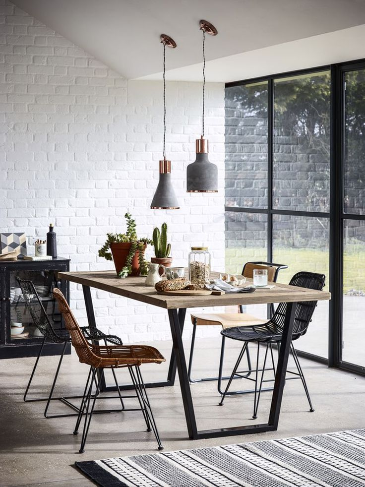 dining space - mismatched chairs paired with raw timber table and copper/grey pendant lights, all set against a white painted brick wall