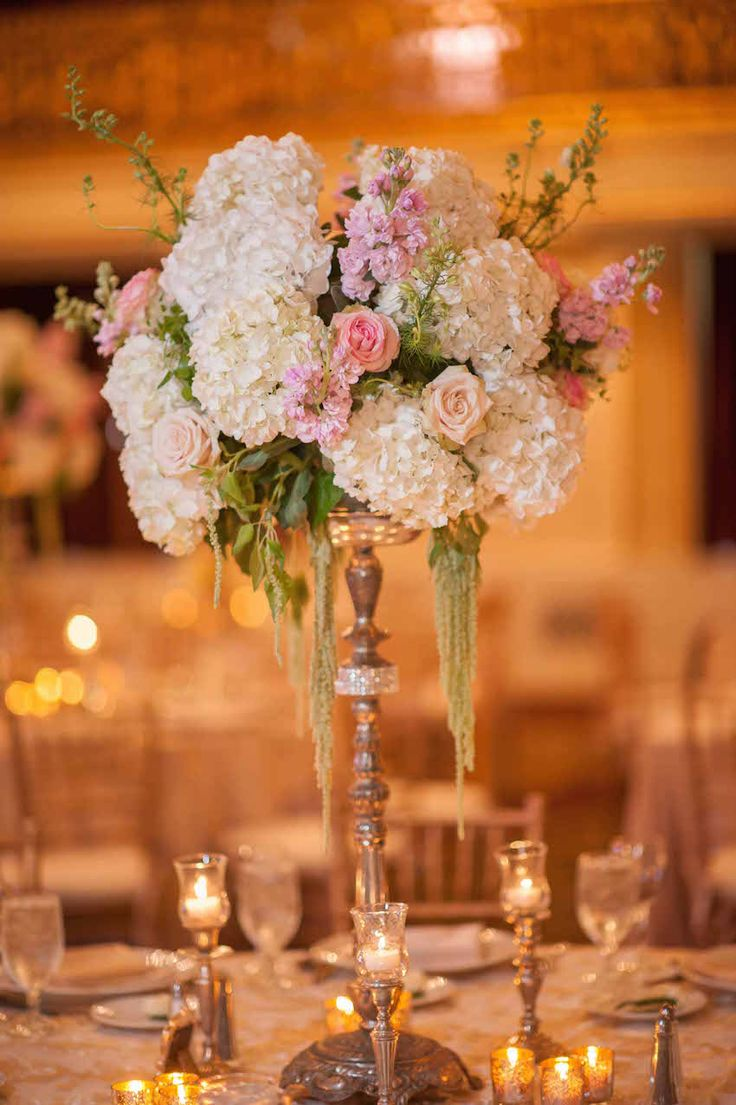 A gilded stand, with a vintage air, brimmed with vanilla hydrangeas, blush and peach roses, green amaranthus, and foliage. #centerpiece #receptiondecor Photography: Palermo Photo. Read More: http://www.insideweddings.com/weddings/bride-wears-isabelle-armstrong-gown-at-classic-pittsburgh-wedding/660/