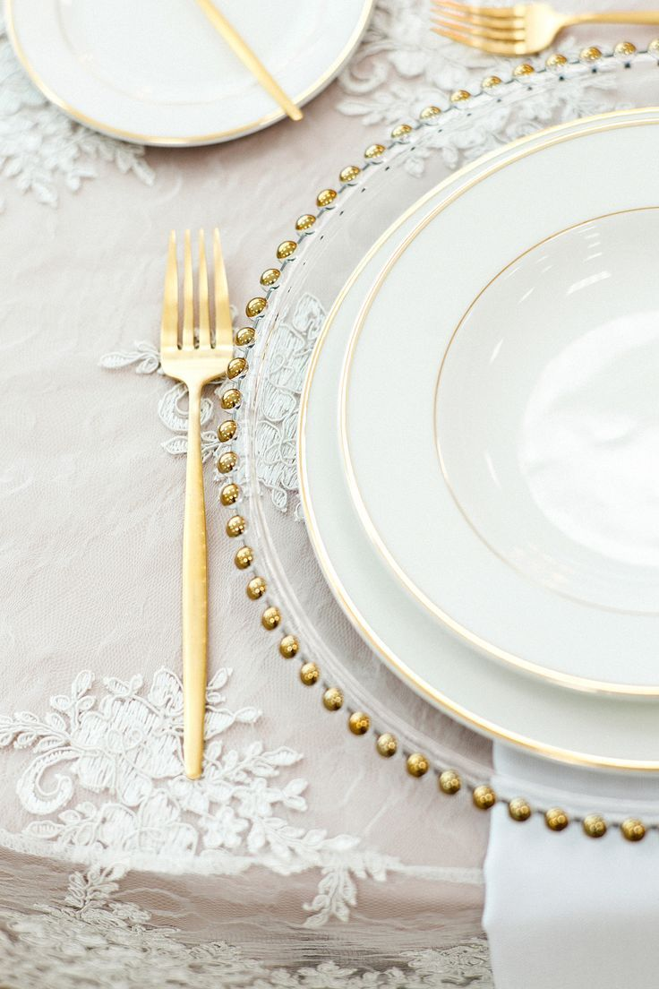 An embroidered white tablecloth atop a cream underlay makes an elegant base for this white and gold theme tablescape. Photographer: @MariaSundinPhotography