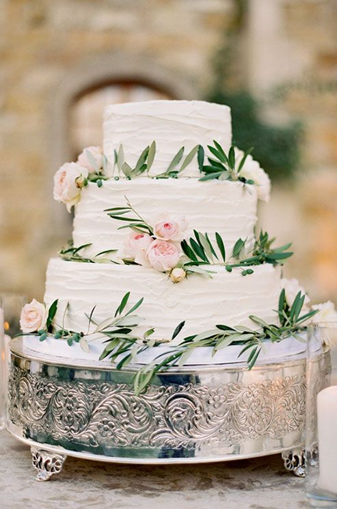 A white textured wedding cake is wrapped in greenery and punctuated with soft pink garden and spray roses.