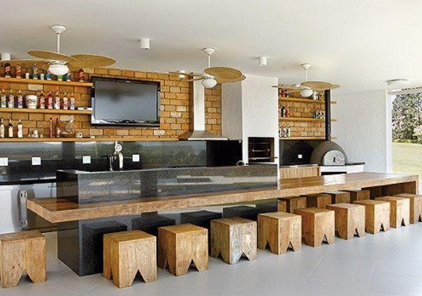 Área de churrasco com bancadas em granito preto e parede de fundo em tijolos tipo demolição. Estantes e mesão em madeira. No blog Assim Eu Gosto.