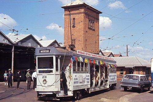 Drop Centre 231, the first Drop Centre Car,, built in 1925, all decorated for the outing of the Brisbane Retired Tramways and Omnibus Old Comrades Association - to the Museum from the Ipswich Road Depot, 12 April, 1969. This was the last outing. Note the variety of men's uniforms, both the old navy and new khaki, but all are wearing caps, not kepis.
