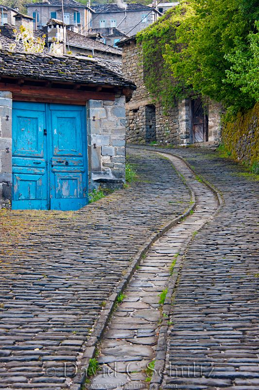 Blue Doors by the Ancient water/sewer canal in the cobblestone street in the village of Vitsa, in the Zagori region of Greece