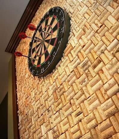 Wine corks recycled into backboard behind dart board. Corks can also be placed inside picture frame for cork board for pinning pictures, notes, car keys, etc.  Use your imagination!