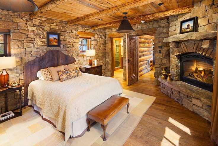 Gorgeous log cabin bedroom, and those stone walls and fireplace are stunning!