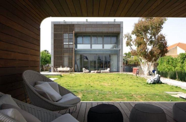 Fotos y planos de la House K, una vivienda de volumen cúbico, realizada con elementos prefabricados de hormigón y celosías de madera. Interior bien decorado y amueblado.