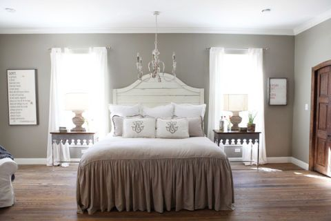 While this room has many of the smart country design decisions we've seen throughout the home, we love its careful symmetry. Decorative side tables are precisely placed underneath tall windows, which bring in plenty of light on either side of the bed.