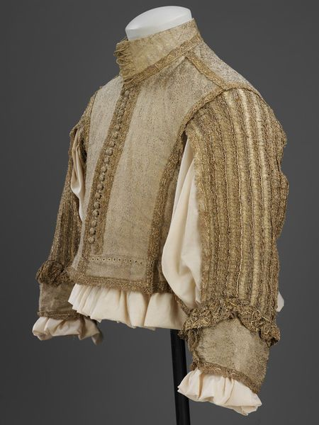 Doublet | British, 1650-1665 | Silver-gilt silk tissue, silver-gilt bobbin lace, silk taffeta, linen | Doublets formed part of the fashionable ensemble of clothing worn by men in Europe until the late 1660's. From 1650 to 1665, doublets shortened so that there was a gap between doublet and breeches through which the shirt could be seen. The centre back and front sleeves were left unstitched for further exposure of the shirt, which in the 17th century was considered underwear | VA Museum…