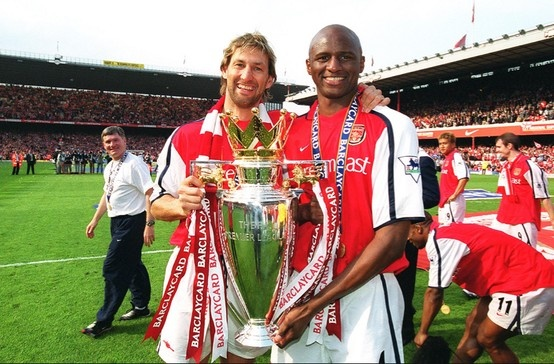 Tony Adams and Patrick Vieira lift the Premiership Trophy at Highbury. Arsenal 4-3 Everton (11 May 2002) by Stuart MacFarlane