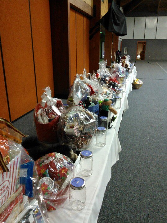 Raffle Items With Mason Jars In Front Of Each Item For Participants