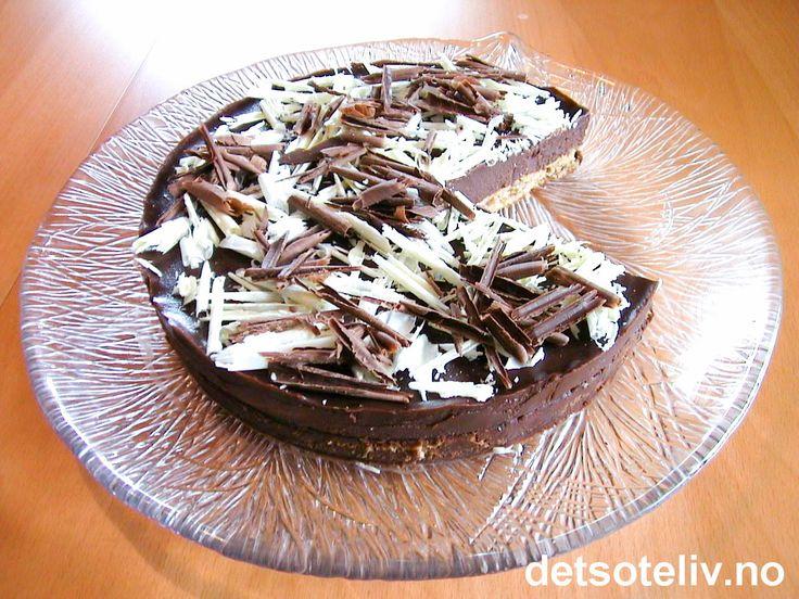 """""""Herrenes konfektkake"""" er en vidunderlig sjokoladekake som består av en luftig kransekakebunn og en mektig, men NYDELIG, sjokoladekrem som de fleste menn (OG damer) elsker! Sjokoladefyllet er laget på mørk sjokolade, kremfløte, smør og rom. Mektig - men himmelsk! Pynten er laget av høvlet mørk og hvit sjokolade, men kan sløyfes. Server kaken i tynne skiver og helst rett fra kjøleskapet."""