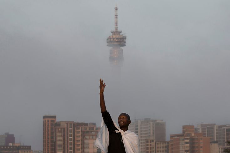 Bernat Armangue—AP Dec. 8, 2013. A Christian worshipper prays on a hill overlooking the city of Johannesburg, South Africa.