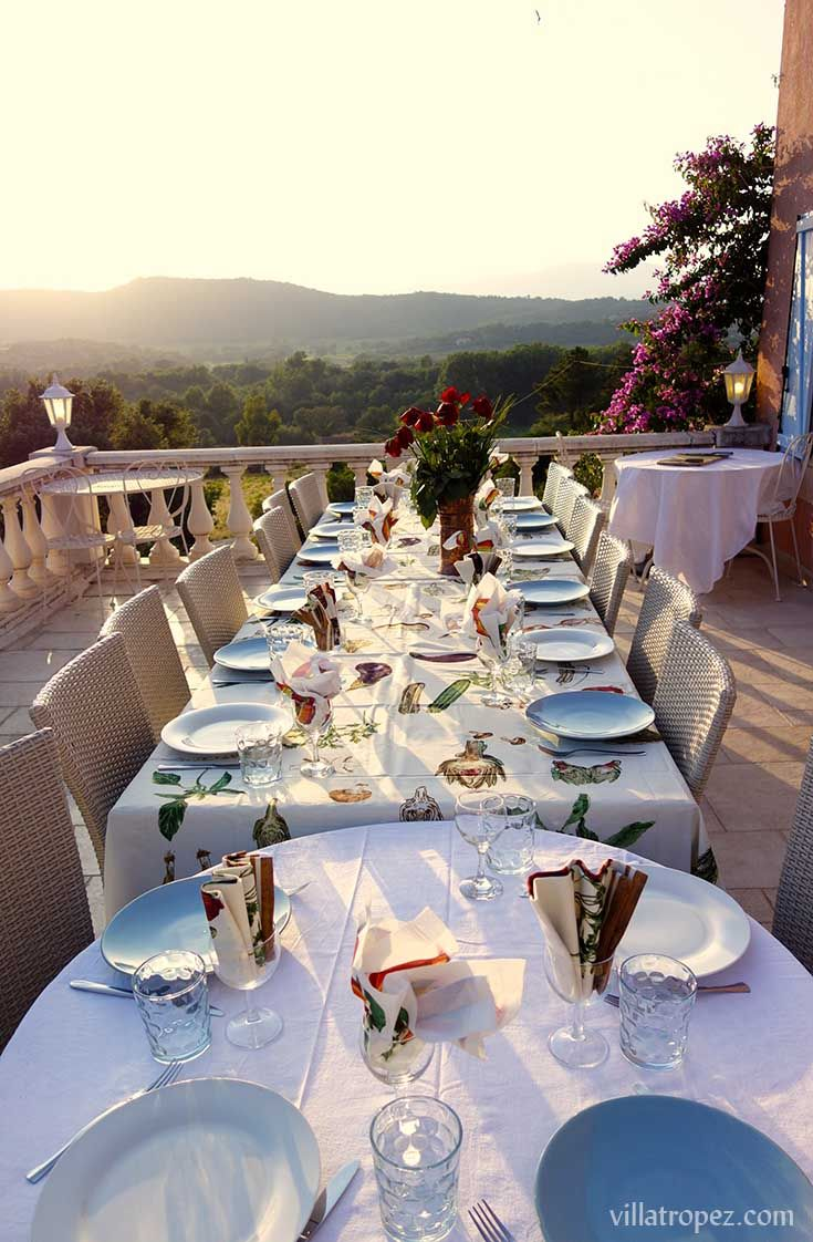 Perfect birthday or anniversary setting. A tablecloth with pictures of french vegetables, and matching serviettes folded & placed in wineglasses, the traditional south-of-France way. The designs reflect the vistas of the Provencal countryside and rolling hills of St Tropez. Imagine entertaining your guests on this balcony, during your celebratory week here!  www.villatropez.com