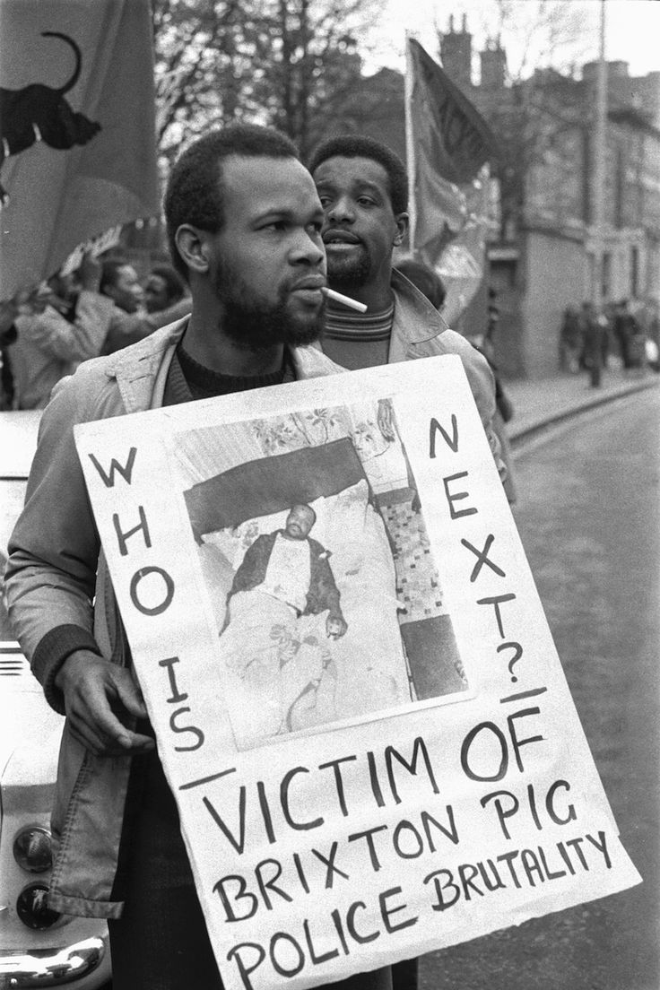 Lost Legacy of the British Black Panthers / Photos: Neil Kenlock / BBP member Eddie Lecointe with a placard raising awareness of police brutality.
