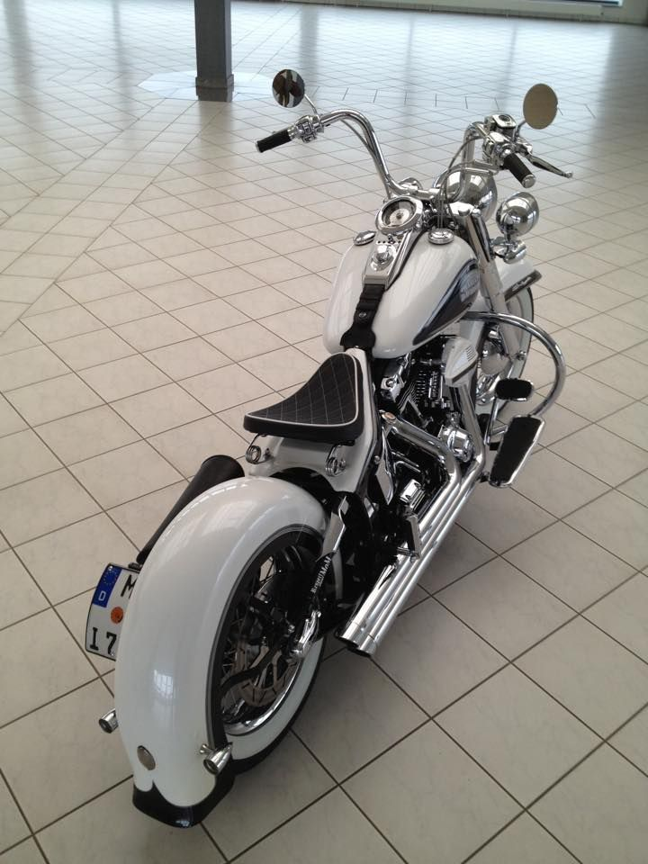 Twin cam Harley Davidson in white with full wrap rear fender, relocated rear turn signals, solo seat sprung solo seat sprung seat, custom Vance & Hines exhaust, mini ape hanger handle bars mini ape hangers