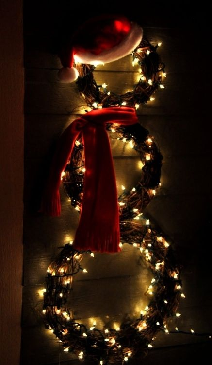What a beautiful idea! DIY snowman by connecting 3 grapevine wreaths, winding lights, and adding a simple hat and scarf!