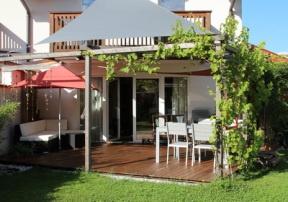5-eckige Terrasse: Esszimmer im Freien und Lounge-Garnitur. Für den Schatten sorgen zwei Sonnensegel und drei Weinstöcke.
