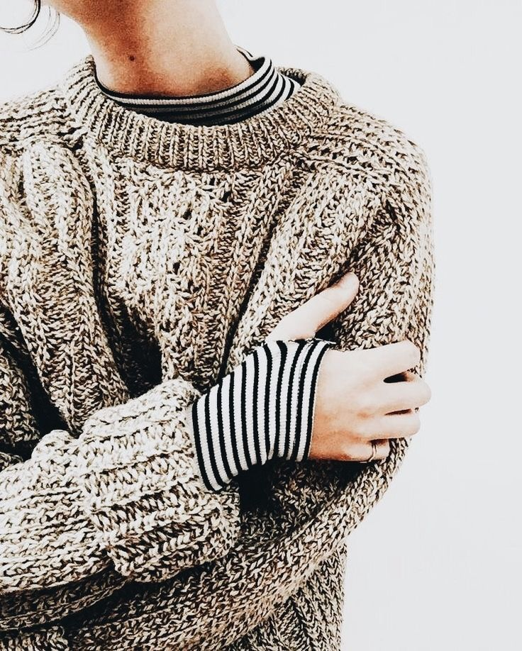 Cozy knit sweater over striped top.