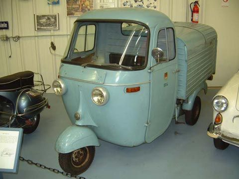 """1963 Vespa Ape. The """"Lastenroller"""" type of vehicle was enormously popular in southern Europe and Italy. The Ape (bee) Model """"A"""" (1948 – 1954) was an open scoter, in three body styles, and was the Model """"B"""" (1955 – 1956) in four body styles. The Model """"C"""" (1956 – 1963) introduced the """"cabin"""" or """"half cabin"""" in no less than eight different body styles. This is a full-cabin, full-box tipper with the double headlamps only seen on German export models."""