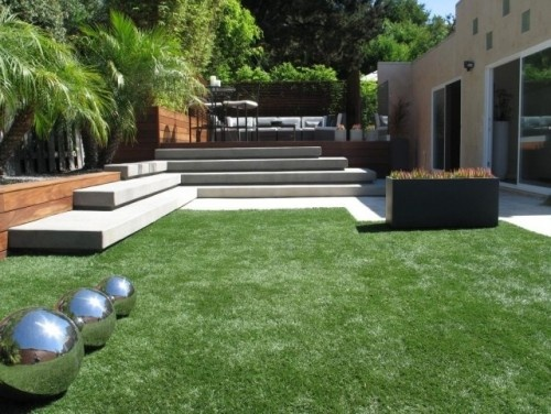 Everything about this landscape exemplifies the best of modern design. Taking each element individually, there are plain concrete steps (that double as seating), a patch of lawn, a raised eating area and plain fencing; in other words, nothing that might seem distinctive. But the sheer overall volume of the steps, the interesting cutout in the expanse of grass and, most of all, the unexpected silver balls, give the entire space a look that is clean, simple and strongly graphic.
