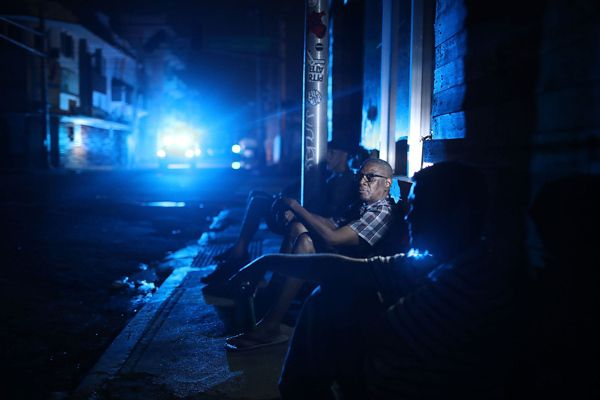 Jaime Degraff sits outside as he tries to stay cool while people wait for the damaged electrical grid to be fixed in San Juan.