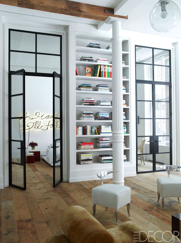 The Philippe Starck chairs in the library were prototypes for the Royalton Hotel, and the custom-made painted steel doors have handles by H. Theophile. - ELLEDecor.com