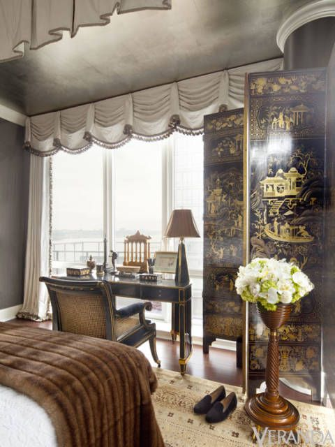 A silver-leafed ceiling creates a jewel-box effect, playing off of the gleaming lacquered walls and strong proportions of the room. Meanwhile, Hampton uses a gilded Chinese screen to downplay an awkward corner column.