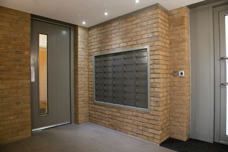 A fire rated wall recessed bank of commercial mailboxes.