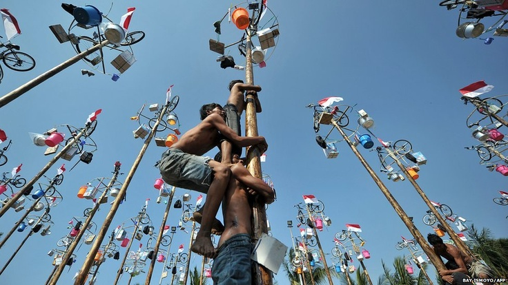 People attempt to climb greased and slippery poles to which prizes and flags are attached, to celebrate Indonesia's Independence Day in Jakarta.