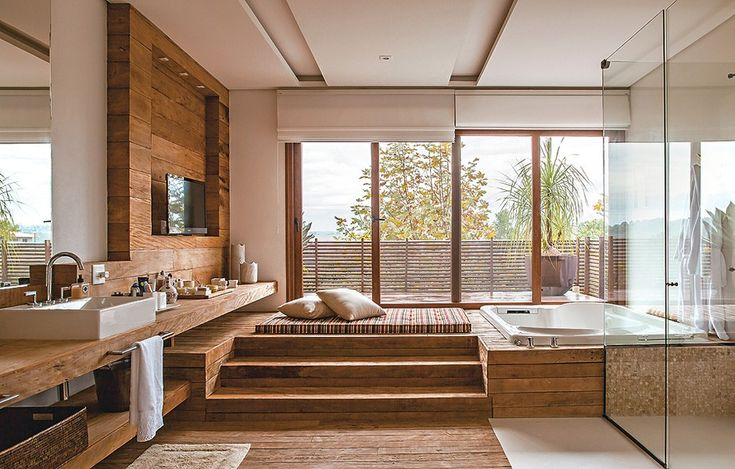 Já pensou tomar banho com vista para a natureza? Isso é possível na casa projetada pela arquiteta Lica Cukier. A banheira foi instalada em uma plataforma para ficar no nível do terraço, separado apenas por grandes portas de vidro
