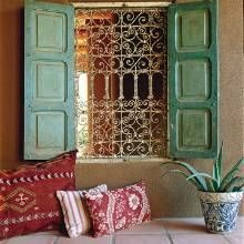Vintage doors and an old iron window grille bring charm to a courtyard.
