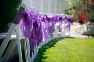 This is a lovely idea that can be used indoors or out (as shown).    We usually think of adding pew markers along the aisle, but what about the plain old chair backs seen at the end of the row as guests are being seated?    Wrap them in purple organza or tulle and tie into beautiful bows. It creates a festive look and gives a nice finish to the ceremony decorations.