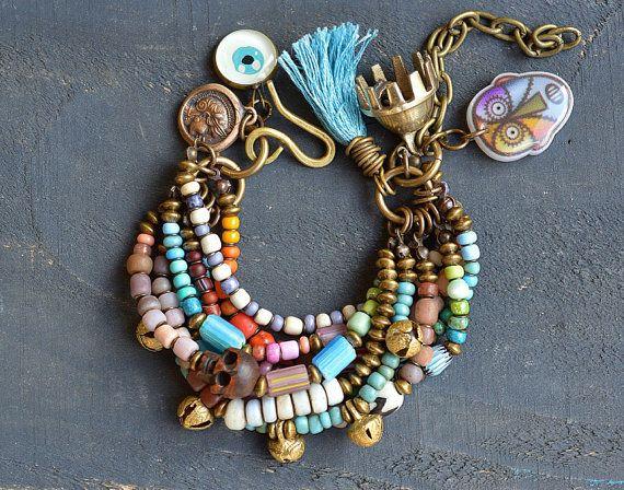 Ich habe diese acht Strängen rustikale Armband mit Handel Perlen, Rocailles, Knochen Perlen, Messing-Abstandhalter, Indien Glöckchen, Vintage afrikanischen Chevron Perlen, eine Hand geschnitzten hölzernen Schädel, eine handgefertigte bösen Blick, eine gegossene Nachbildung von einer antiken griechischen eine große gezahnten Indien Glocke und eine handgemachte Baumwolle tassel Münze. Die Messing-Haken-Verschluss ist handgefertigt. Das Armband ist einstellbar, um die meisten Handgelenke…