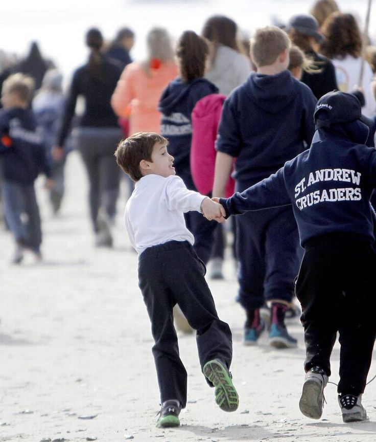 About 250 children from St. Andrew Catholic School participate in a three-mile walk from the church and up the beach in the fifth annual Beach Walk to Stamp Out Hunger.