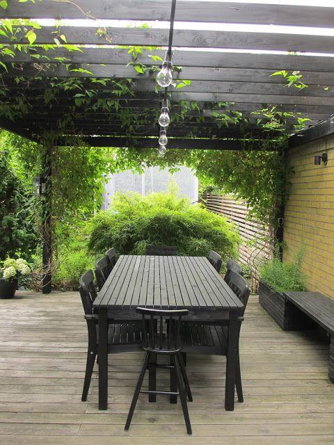 Pergola, sittbänk, växtkärl – allt snickeri samma färg binder ihop (svart passar bra till gult tegelhus). Hängande lampor (som dock säkerligen bländar).
