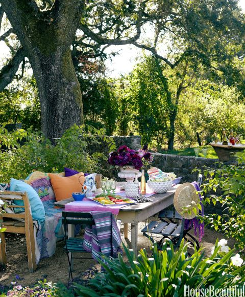 In a California wine country house designed by Stephen Shubel, homeowner Gabriella Sarlo sometimes commandeers furniture from her cellar and sets it up outside for alfresco dining under century-old oak trees. The table, chairs, white bowls, and settee are from Chateau Sonoma. The rug over the settee is from Anthropologie, as are the glasses, purple bowl, and pitcher. The urn holding flowers is a French antique from stephenshubel.com.