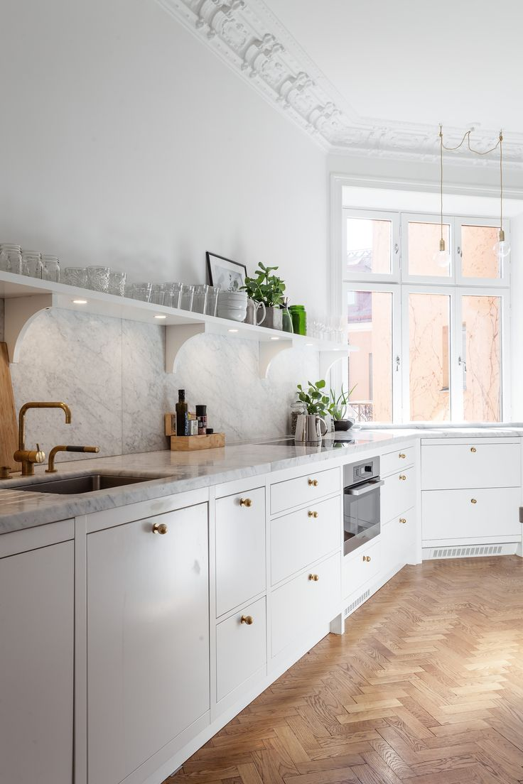 Bright Stockholm apartment kitchen with crown molding, herringbone floors, and marble countertops