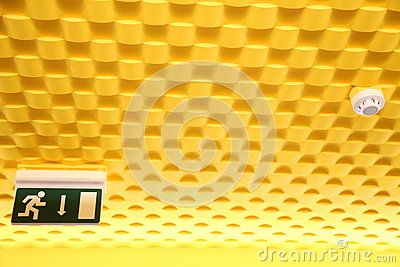 Exit sign and smoke detector on yellow textured ceiling.